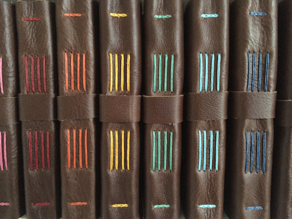 Spines of Chocolate Brown Leather Journals Sewn with different thread colors
