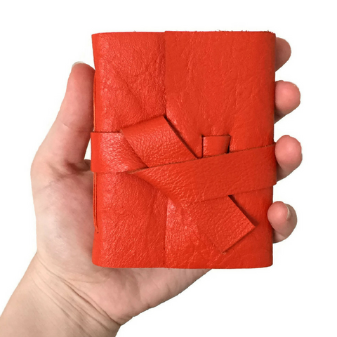 Mini Orange Notebook in someones hand