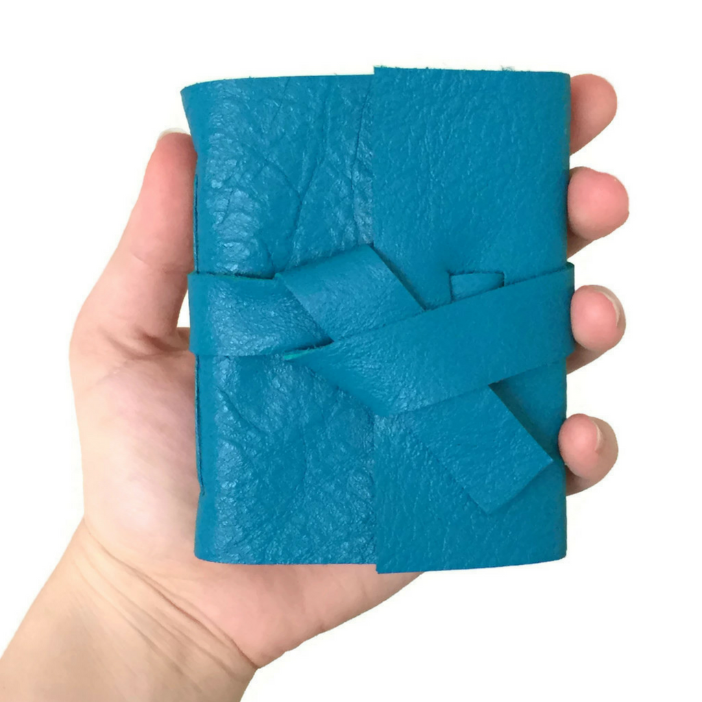 Teal mini notebook in someones hand