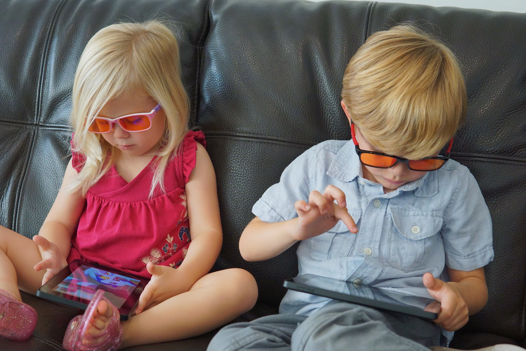 Two Children Using Digital Devices and Wearing Blue Light Blocker Glasses