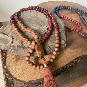 "Mala #3 - Made with natural wood beads and and brown, rust, and cranberry dyed wood beads, an oval shaped, Red Creek Jasper guru stone and a cotton 2"", light brown colored tassel with a silver accent."