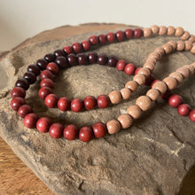 "Mala #5 - Made with natural light wood beads, rust and cranberry dyed wood beads, an oval shaped, Mookaite Jasper guru stone and  cotton, 2"", brown colored tassel."