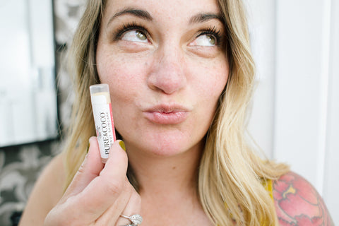 woman holding a moisturizing coconut lip balm