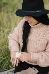 Woman wearing a hat, applying lotion to her bare hand