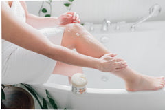 Woman applying a body exfoliator to her legs by Pure & Coco