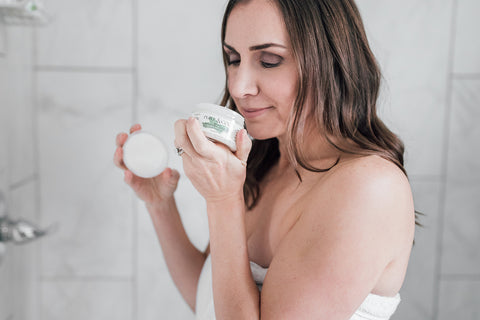 Woman standing in shower with sugar scrub smelling it