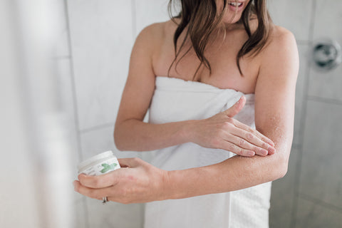 Woman standing in shower exfoliating her arm