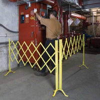 Safety Yellow Expanding Heavy-Duty Portable Aisle Gates surrounding machinery and worker