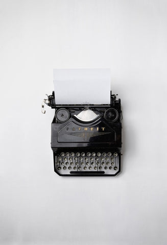 Typewriter with blank page on white table