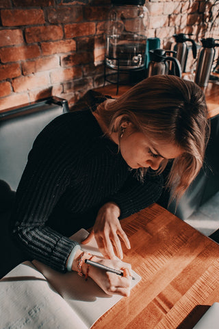 Girl in a cafe writing in a journal on a wooden table