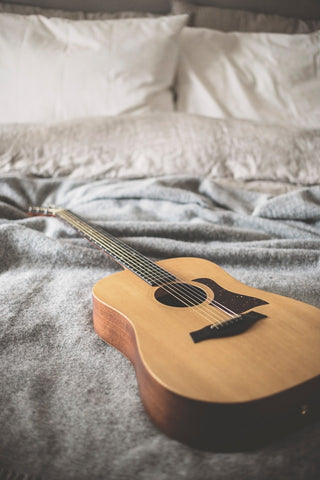 Acoustic guitar on bed with white sheets