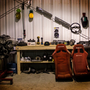 Portrait of Jimmy Oake's garage, showing red sparco racing seats, a black Nardi steering wheel, DeWalt power tools, and pineapples.