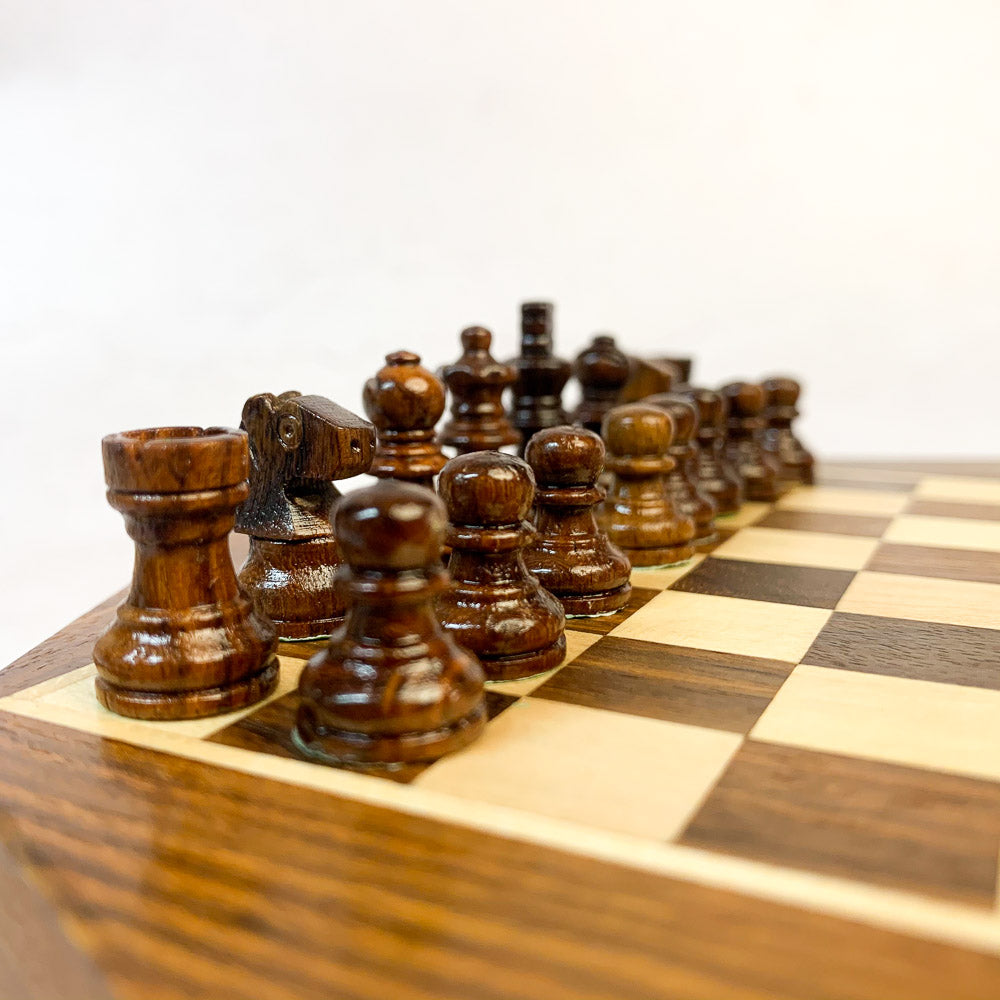 Dark chess pieces laid out on wooden board ready for play.