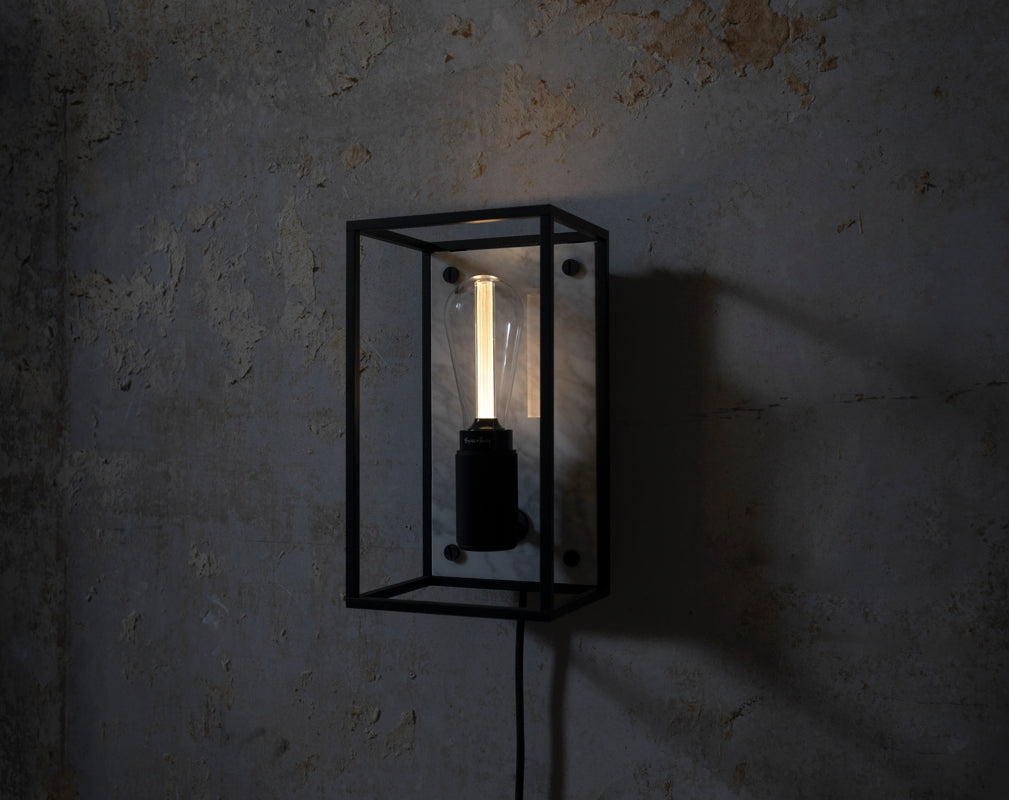 A Buster + Punch CAGED wall light illuminates an industrial backdrop