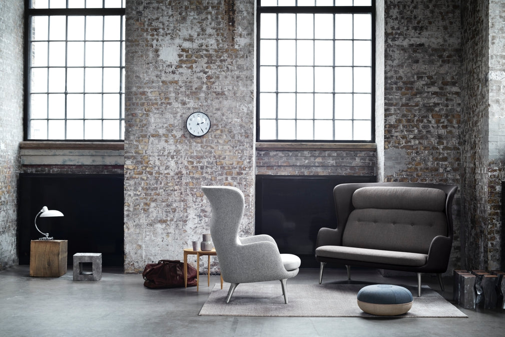 An industrial chic living room features designs by Fritz Hansen including the 7263 Ro Sofa in Dark grey