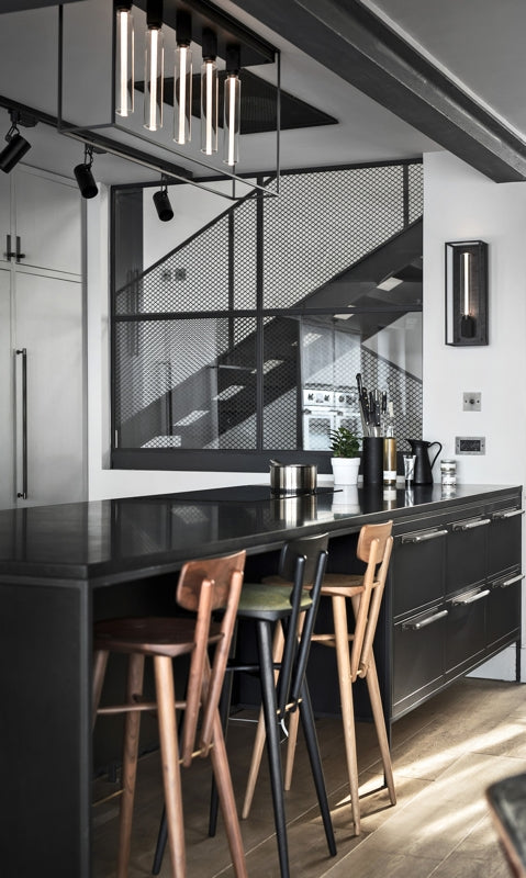 Angled view of an industrial chic kitchen featuring CAGED lighting by Buster + Punch