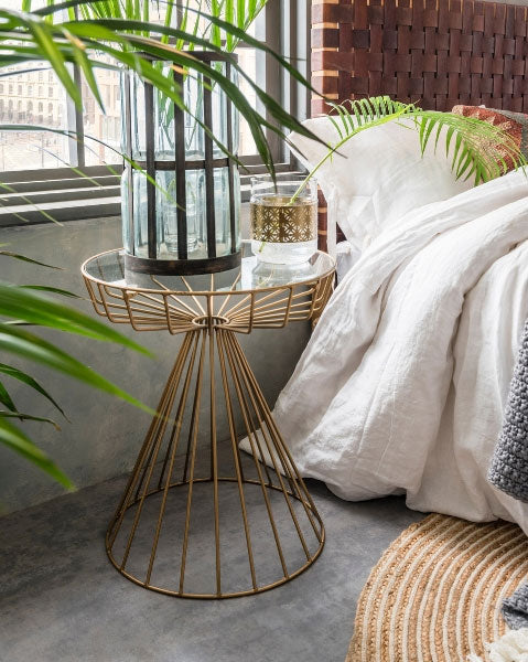 Gatsby Birdcage Side Table has an antique gold finish, a striking geometric base and glass tabletop. Available from Cuckooland