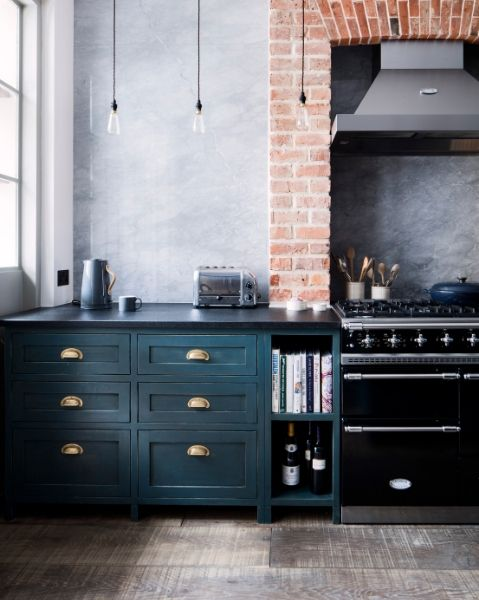 Industrial style Kitchen featuring range cooker against exposed brick wall. Havwoods weathered rustic surface flooring