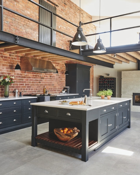 Industrial style shaker kitchen against exposed brick wall with steel beams overhead and indutrial lighting. Kitchen by Tom Howley.