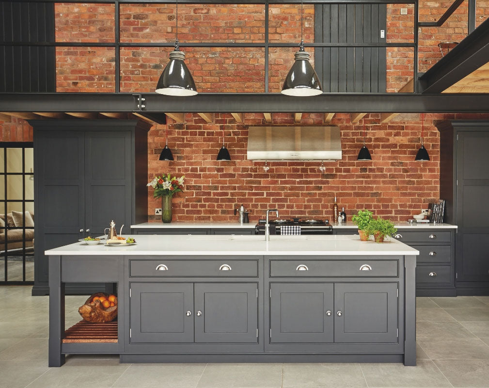 Industrial style shaker kitchen painted in charcoal grey against an exposed brick wall and featuring lots of original features. Kitchen by Tom Howley