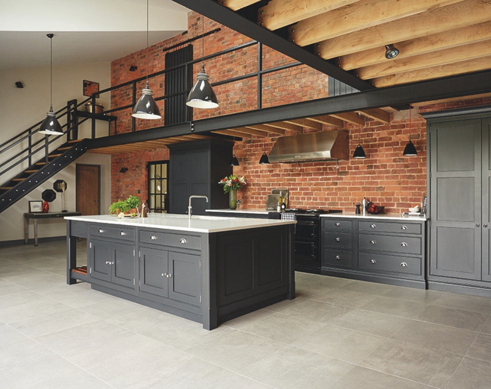 An industrial style shaker kitchen in charcoal grey complements the steel structure in the room and contasts with the exposed brick wall. Kitchen by Tom Howley.