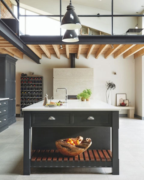 An industrial style shaker kitchen in front of a concrete fireplace. Kitchen by Tom Howley.