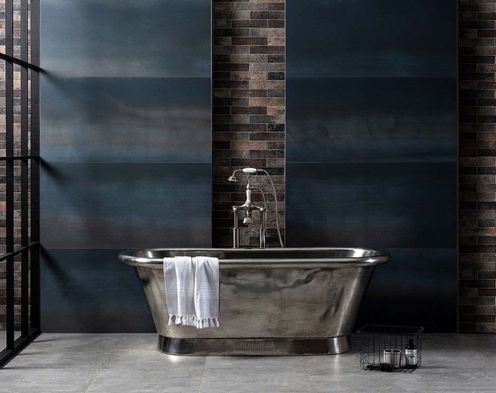 Industrial style bathroom featuring a freestanding nickel bathtub and extra large format blue metal effect porcelain wall tiles