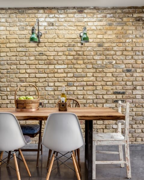 Exposed brick walls and industrial wall lighting are the main features of this dining area