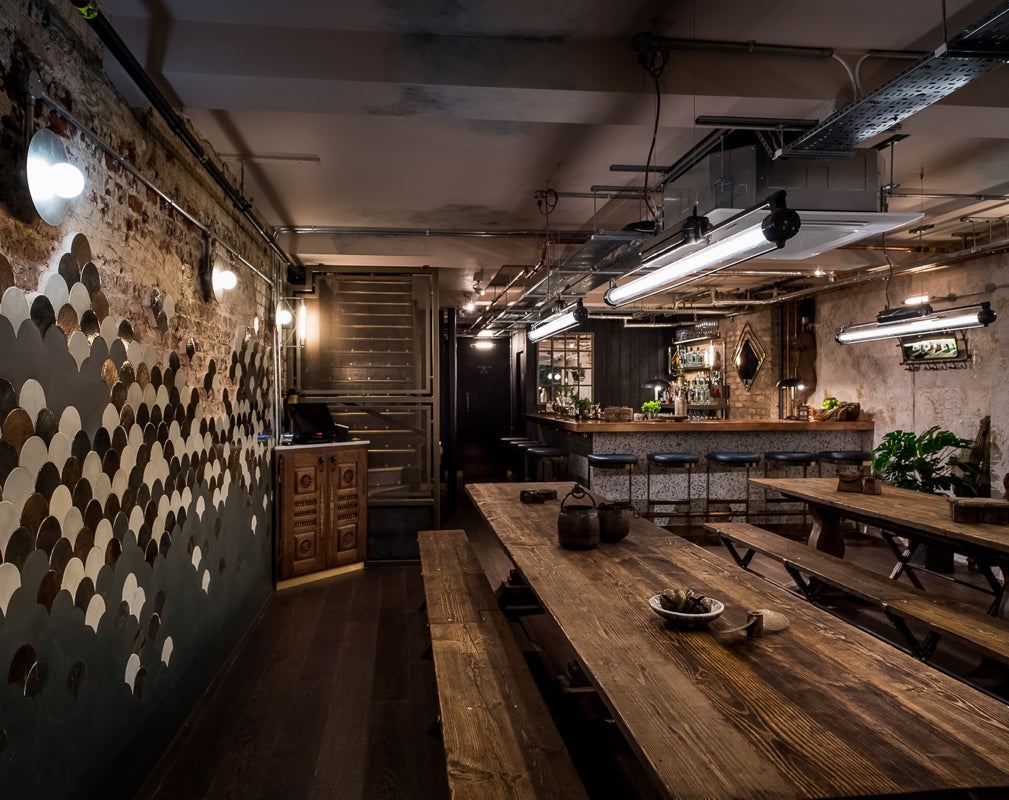 Rustic communal tables feature at Kricket Soho in London designed by Run For The Hills