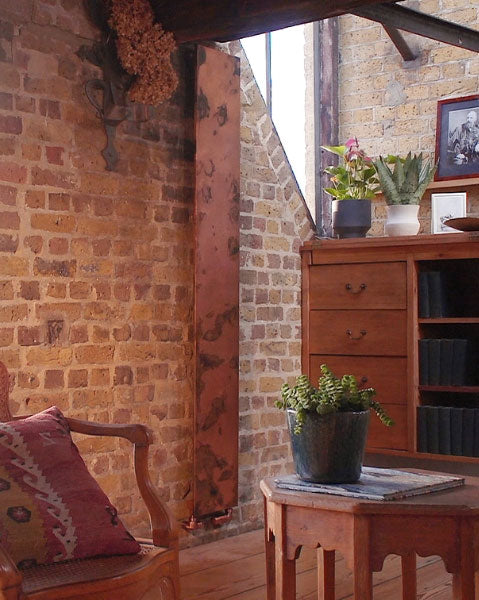 The Arteplano acid etched copper radiator from Bisque Radiators on an exposed brick wall in a converted warehouse home