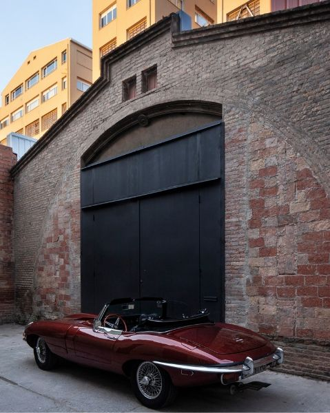 The Theatre converyed warehouse by Cadaval Sola-Morales. The red brick exterior has a large metal swing doors to give access to the classic car.
