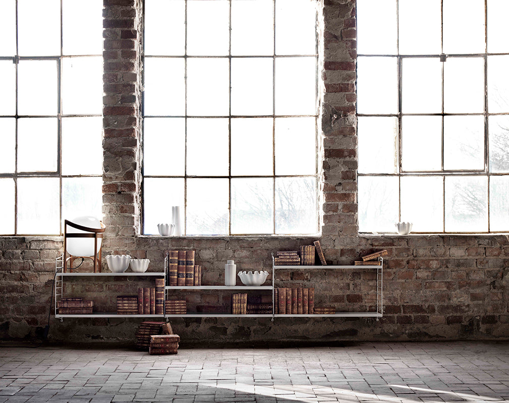 wall mounted shelving in a warehouse conversion with exposed brick wall and warehouse windows.
