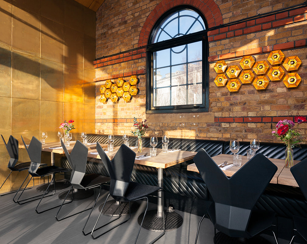 exposed brickwork and brass features in the restaurant interior of the dock kitchen by tom dixon