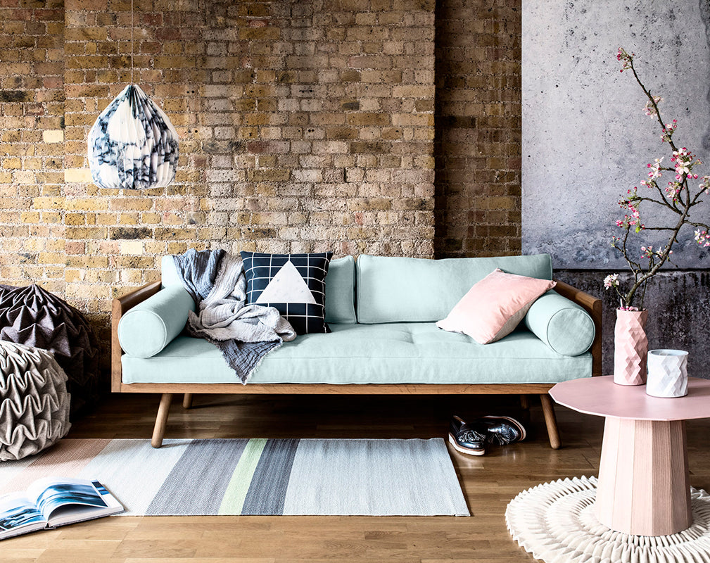Pastel coloured interior living room scheme in a converted warehouse with raw brickwork