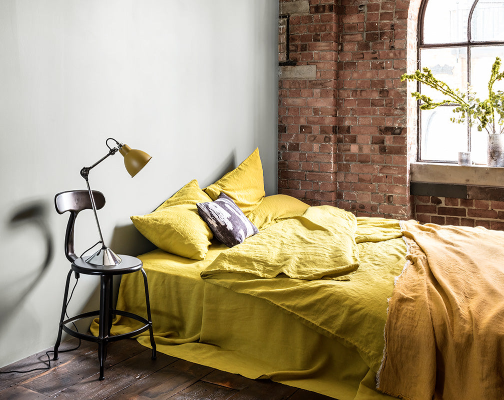 Stylish bedroom in a converted warehouse with exposed brick wall and warehouse window
