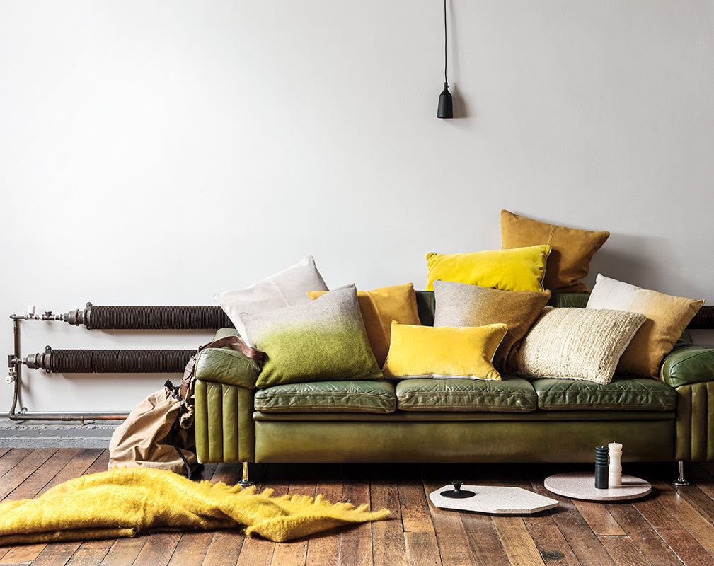 Vintage green sofa with yellow and green cushions and matt black pendant