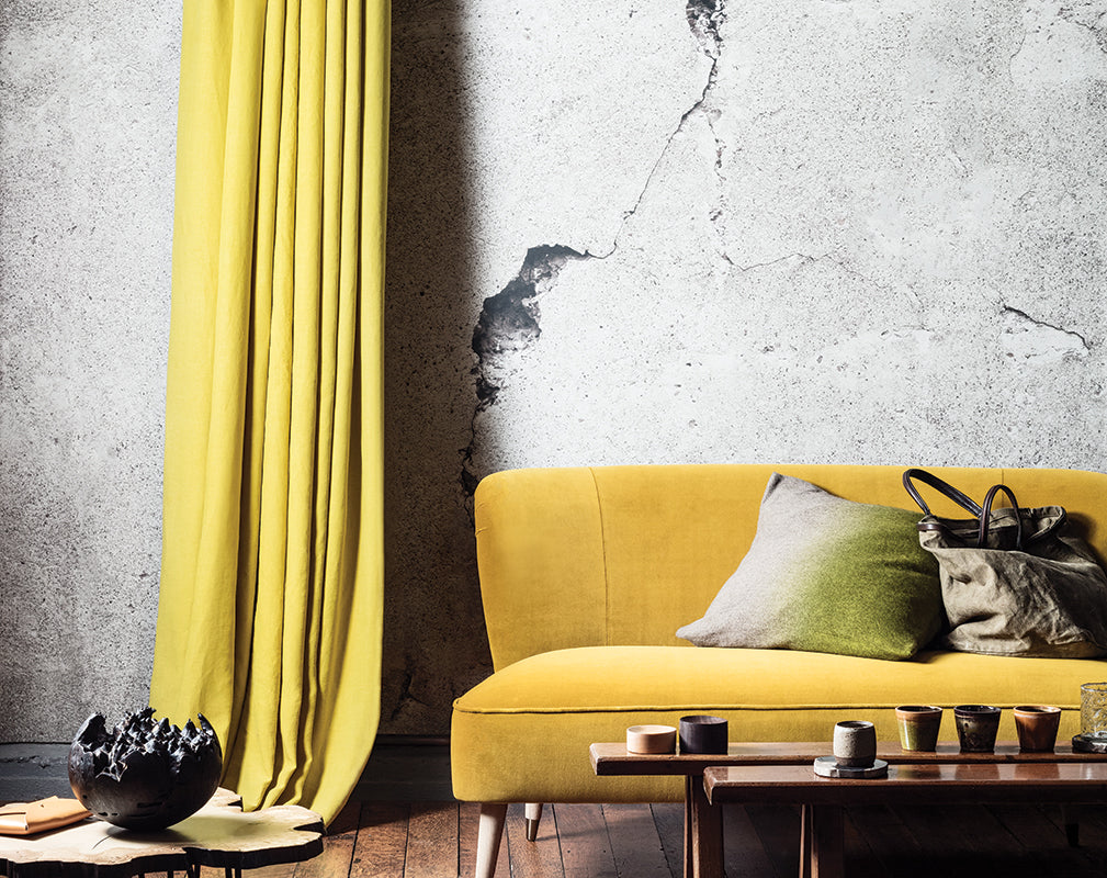 interior living room scheme with cracked concrete wall mural and ochre yellow accents