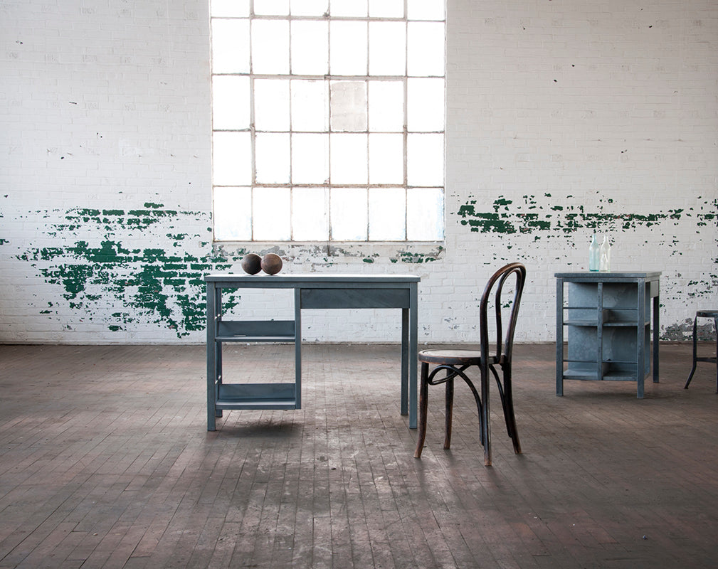Vintage Bel Geddes minimalist trestle desk against exposed warehouse brick.