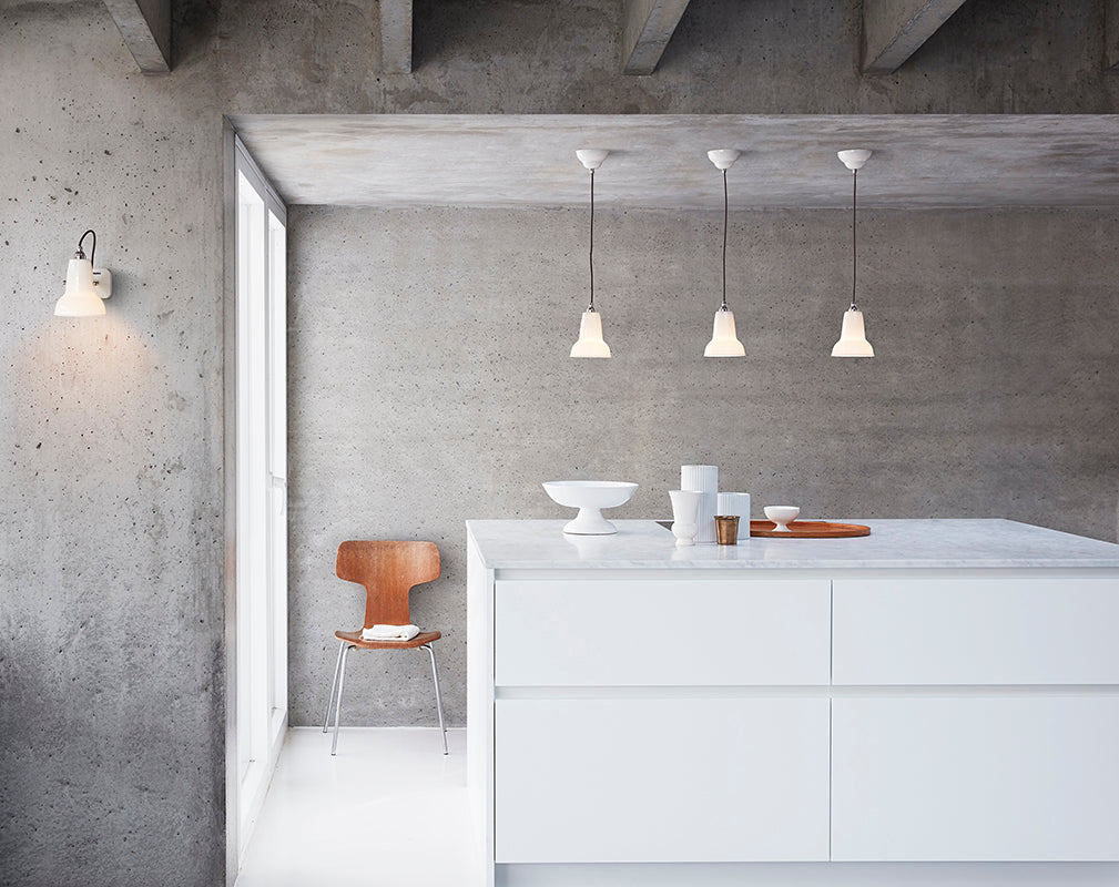 Concrete interior walls and beams with ceramic anglepoise pendants.