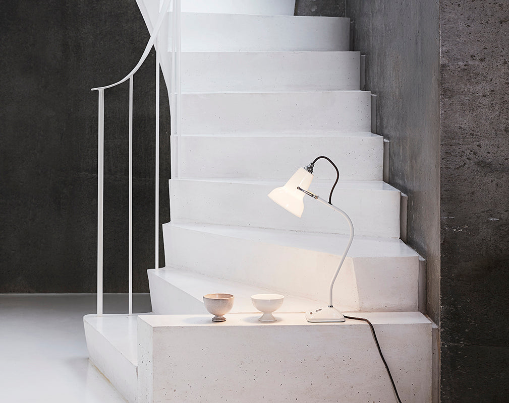 Anglepoise Original 1227 mini ceramic table lamp on raw concrete staircase.