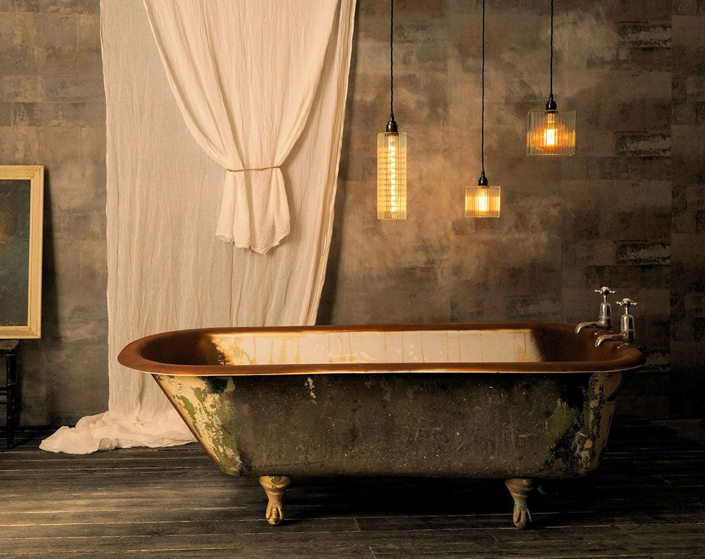 redeed glass pendants from the light yard suspended over a vintage bathtub.