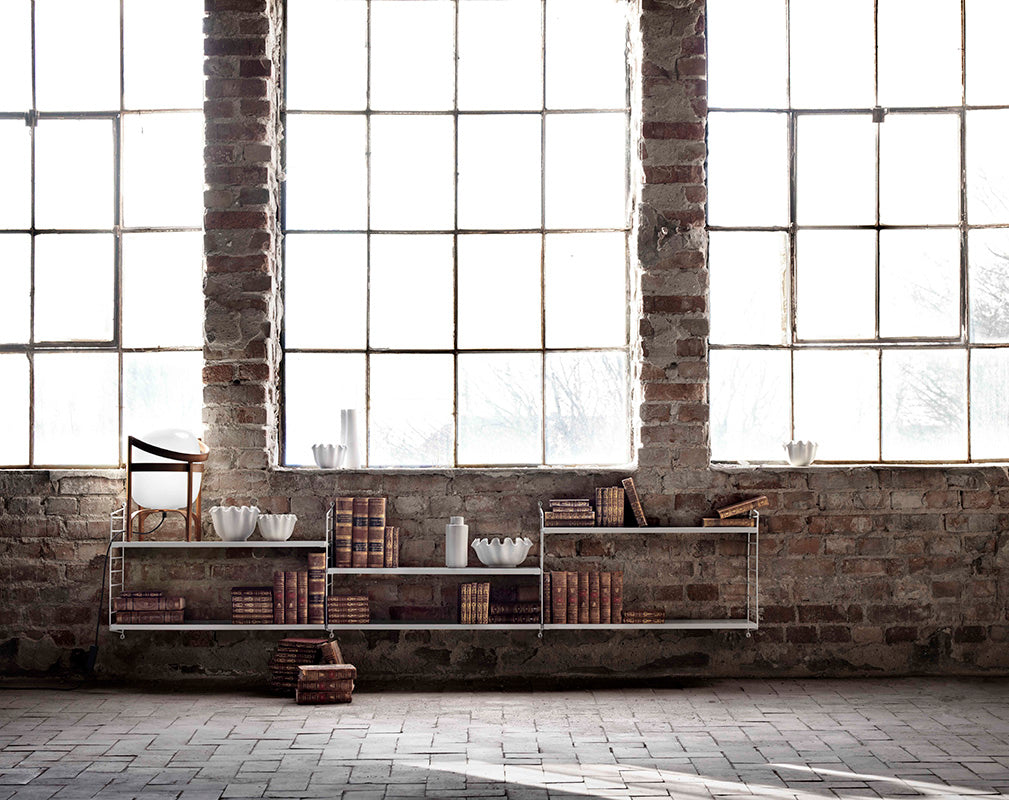 Large warehouse window, exposed brick and low storage unit from String furniture