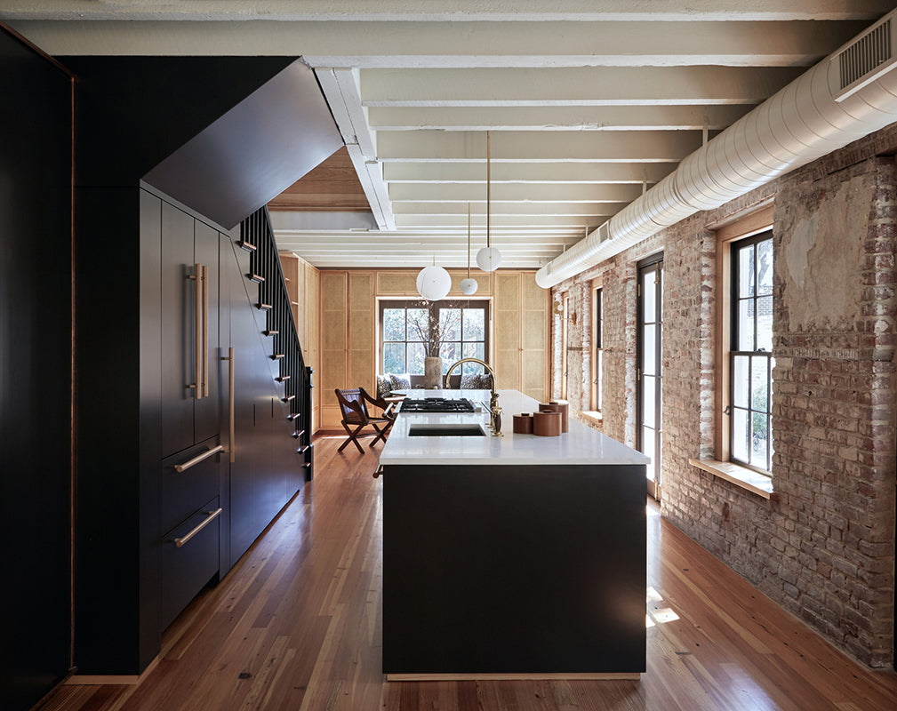 a minimalist kitchen scheme complements original brick and exposed beams