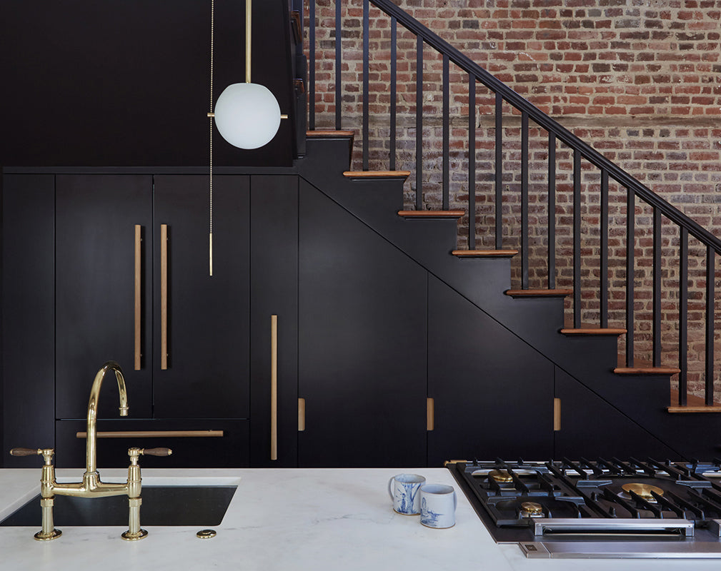 a sleek black staircase serves as a focal point in this converted industrial building