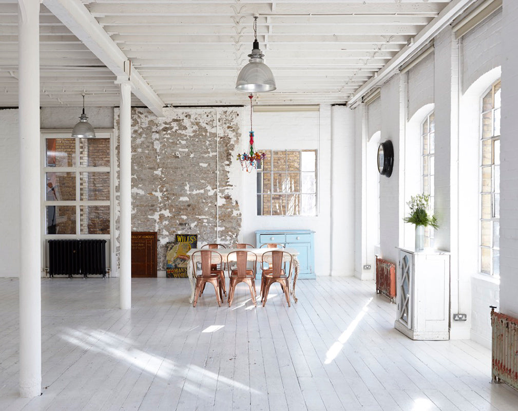 converted warehouse in london with painted white brickwork and vintage industrial furniture.