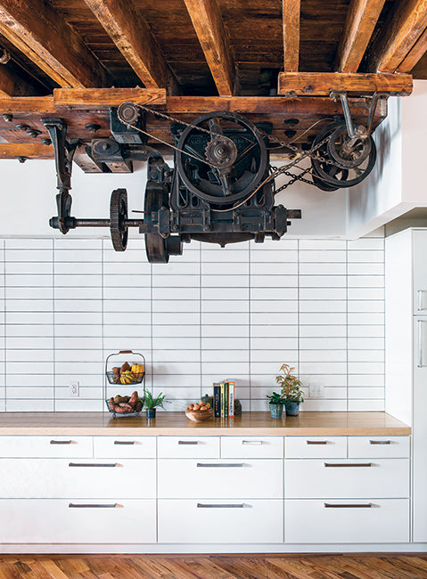 Kitchen In A Warehouse Conversion Features Large Industrial Motor As  Decoration.