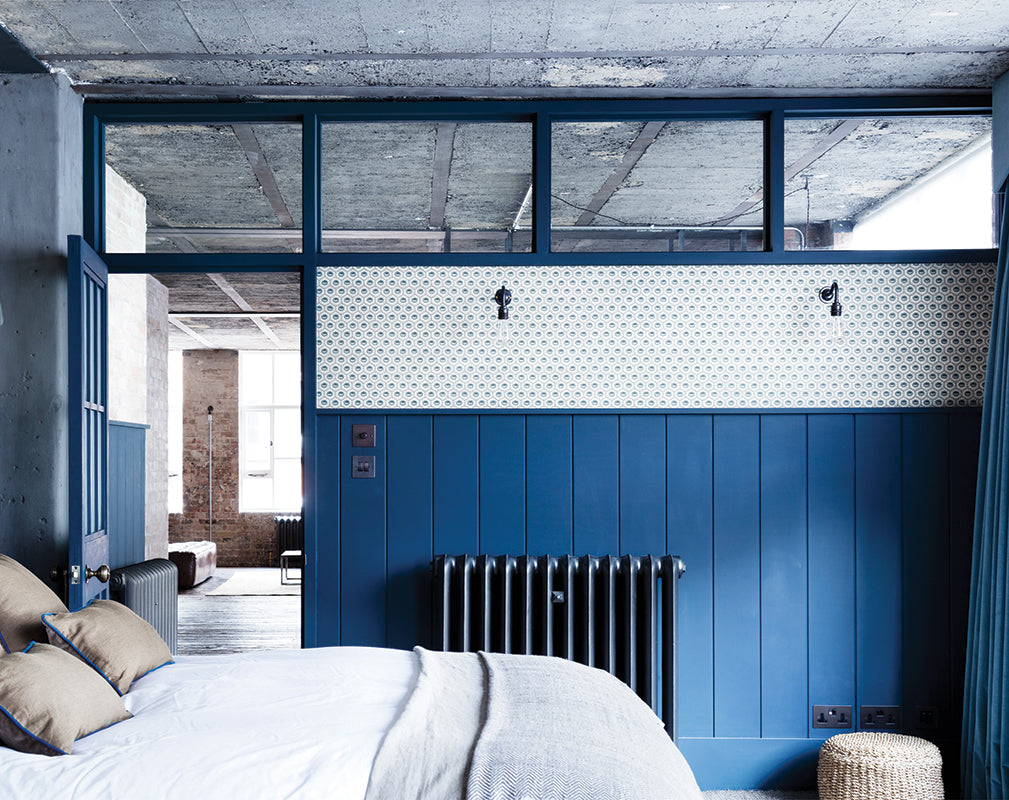 bedroom in a london warehouse conversion with exposed brick and raw concrete ceiling.