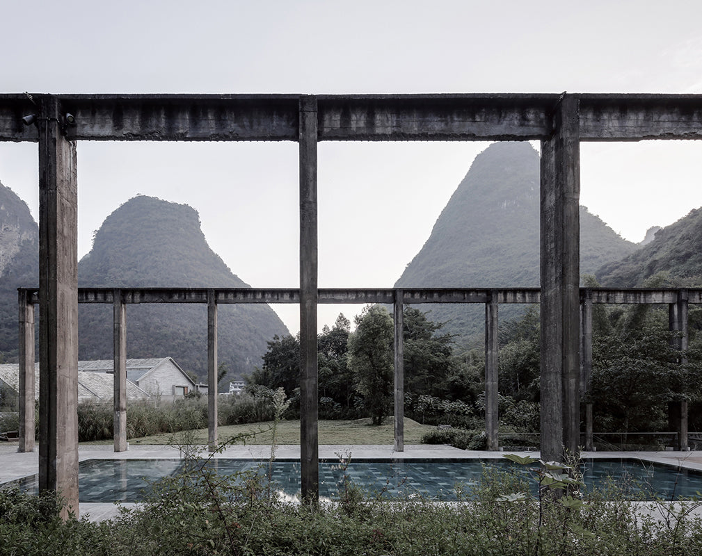 concrete pylons frame an outdoor pool at alila yangshuo, a converted sugar factory cum hotel in china photography by Shengliang  Su