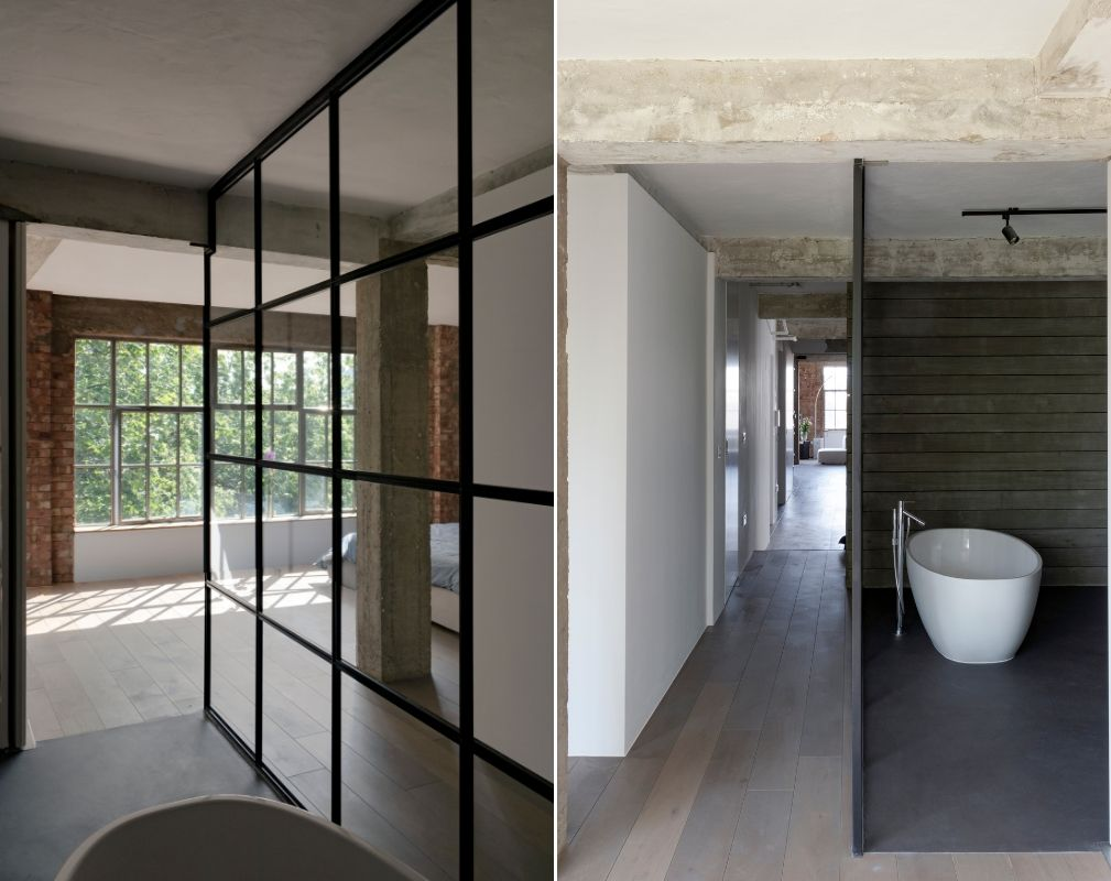 The ensuite master bathroom appears open-plan to the bedroom in this converted warehouse home by William Tozer Associates