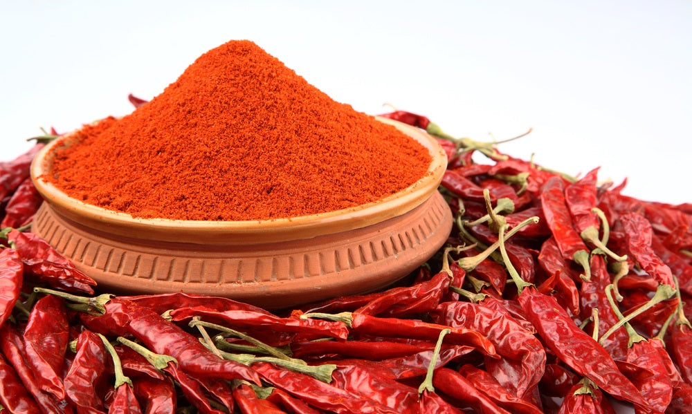 Bowl of cayenne pepper surrounded by red peppers